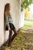 Façonnez la fille avec de longs cheveux utilisant la jupe noire, le manteau de fossé et la veste en cuir grise Image stock