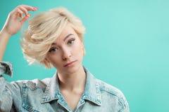 Façonnez la fille blonde fixant ses cheveux pendant le matin avant travail photos stock