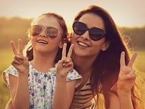 Façonnez la fille d'enfant embrassant sa mère dans les lunettes de soleil à la mode et le s Photo libre de droits