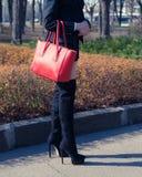 Façonnez la fille de blogger posant dans la rue dans tendre noir d'un costume, bottes à talons hauts et un grand sac à main rouge Images libres de droits