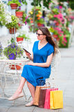 Façonnez la fille heureuse avec des sacs après café potable de achat en café en plein air Vente, consommationisme et concept de p Images libres de droits