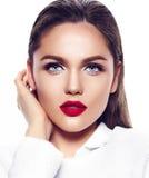 Façonnez la fille modèle sexy dans le manteau blanc avec les lèvres rouges Photo stock