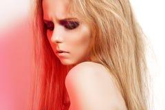 Façonnez la fille sombre avec le renivellement dans la lumière rouge de roche Photographie stock