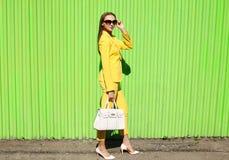 Façonnez la jeune femme élégante dans des vêtements jaunes de costume avec le sac à main image stock