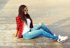 Façonnez la jeune femme africaine s'asseyant en parc de ville, utilisant les lunettes de soleil à carreaux rouges d'une chemise Images libres de droits