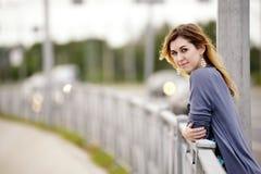 Façonnez la jeune femme avec la main sur des balustrades posant dans l'espace urbain industriel photos stock