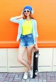 Façonnez la jolie femme avec une planche à roulettes dans la ville au-dessus de coloré orange image libre de droits
