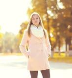Façonnez la jolie femme portant un manteau rose en parc d'automne image libre de droits