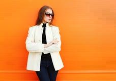 Façonnez la jolie jeune femme utilisant une veste blanche de manteau contre l'orange photographie stock libre de droits