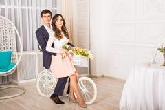 Façonnez la photo des couples affectueux élégants posant au studio avec l'intérieur classique près de la bicyclette Photos stock