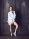 Façonnez la veste blanche de port, les shorts et les espadrilles de femme posant contre la porte Image libre de droits