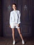 Façonnez la veste blanche de port, les shorts et les espadrilles de femme posant contre la porte Photos libres de droits