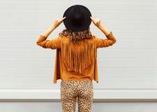 Façonnez la vue de femme du dos utilisant un chapeau noir, les lunettes de soleil et la veste au-dessus du fond urbain photos stock