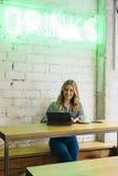 Façonnez le blogger travaillant au media social et ayant une boisson Photographie stock libre de droits