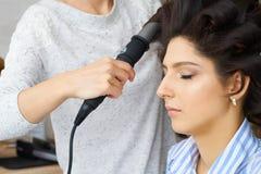 Façonnez le coiffeur faisant la coiffure au client de jeune femme faisant à permanente le styler professionnel pour la boucle images libres de droits