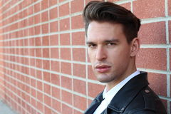 Façonnez le jeune homme dans la chemise blanche et la veste en cuir noire au-dessus du mur de briques brouillé moderne avec l'esp Photo stock