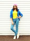 Façonnez le joli modèle de femme dans des vêtements colorés au-dessus du fond blanc utilisant les lunettes de soleil roses de jau Photo libre de droits