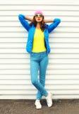 Façonnez le joli modèle de femme dans des vêtements colorés posant au-dessus du fond blanc utilisant les lunettes de soleil roses Photos stock