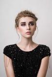 Façonnez le modèle blond avec la robe noire regardant loin Image libre de droits