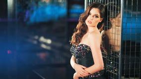Façonnez le modèle de femme élégante dans la belle robe posant au-dessus du fond rougeoyant de nuit clips vidéos