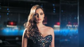 Façonnez le modèle de femme élégante dans la belle robe posant au-dessus du fond rougeoyant de nuit banque de vidéos