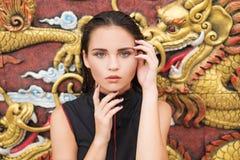 Façonnez le plan rapproché de la jeune femme de brune au-dessus du dragon d'or sur le mur photo libre de droits