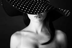 Façonnez le portrait d'une femme avec les lèvres noires et blanches de chapeau et de tacaud de points Image stock
