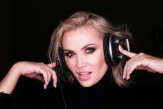 Façonnez le portrait d'une femme dans des écouteurs au-dessus de bsckground noir photo stock