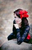Façonnez le portrait d'une femme dans la dentelle noire avec les fleurs rouges sur le fond en pierre Photos libres de droits