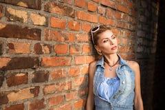 Façonnez le portrait d'une fille à un mur de briques Photos libres de droits
