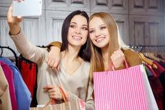 Façonnez le portrait de deux jeunes belles amies de femmes dans le centre commercial avec beaucoup de paniers Fabrication du self Photographie stock libre de droits