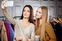 Façonnez le portrait de deux jeunes belles amies de femmes dans le centre commercial avec beaucoup de paniers Fabrication du self Images stock