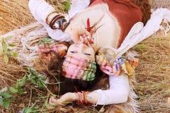 Façonnez le portrait de femme de style de boho, appréciez l'été se trouvant sur un foin photographie stock libre de droits