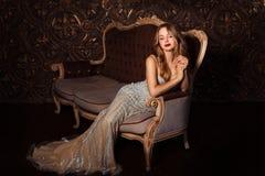 Façonnez le portrait de la femme attirante dans la robe élégante posant à l'intérieur de la manière sensuelle Photographie stock libre de droits