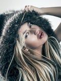 Façonnez le portrait de la femme blonde attirante dans le capot de manteau de fourrure Image stock