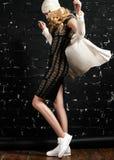 Façonnez le portrait de la fille à la mode avec les cheveux blonds, en utilisant une robe et une veste noires se tenant contre le Photo libre de droits