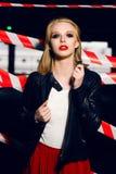 Façonnez le portrait de la fille blonde sexy avec les lèvres rouges portant un style de noir de roche posant sur le fond du dispo Photos stock