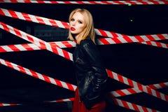 Façonnez le portrait de la fille blonde sexy avec les lèvres rouges portant un style de noir de roche posant sur le fond du dispo Photos libres de droits