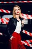 Façonnez le portrait de la fille blonde sexy avec les lèvres rouges portant un style de noir de roche sur le fond du dispositif a Image libre de droits
