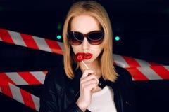 Façonnez le portrait de la fille sexy avec la sucrerie à disposition portant un style de roche, lunettes de soleil sur le fond du Photographie stock