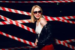 Façonnez le portrait de la fille sexy utilisant un style et des lunettes de soleil de noir de roche posant sur le fond du disposi Image libre de droits