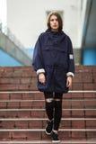 Façonnez le portrait de la jolie femme élégante posant sur la rue dans le jour nuageux Équipement urbain à la mode de port, longu Image stock