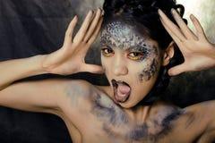 Façonnez le portrait de la jolie jeune femme avec créatif composent comme un serpent Photographie stock