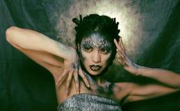 Façonnez le portrait de la jolie jeune femme avec créatif composent comme un serpent Photo stock