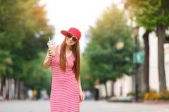 Façonnez le portrait de ville de la femme élégante de hippie avec le lait de poule, la robe rayée rouge, le chapeau rouge et les  Images libres de droits