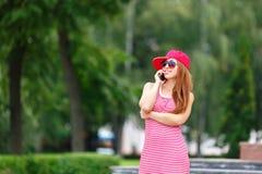 Façonnez le portrait de ville du téléphone portable parlant de femme élégante de hippie, de la robe rayée rouge, du chapeau rouge Photographie stock libre de droits