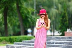 Façonnez le portrait de ville du téléphone portable parlant de femme élégante de hippie, de la robe rayée rouge, du chapeau rouge Photo stock