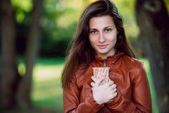 Façonnez le portrait extérieur de la longue femme magnifique de cheveux dans la veste en cuir brune avec la tasse de coffe Fille  photo stock