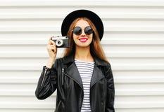 Façonnez le regard, joli modèle de jeune femme avec le rétro appareil-photo de film utilisant le chapeau noir élégant, veste en c Images libres de droits