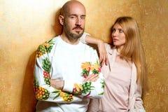 Façonnez le type avec une fille dans le studio posant sur un backgroun d'or Photographie stock libre de droits